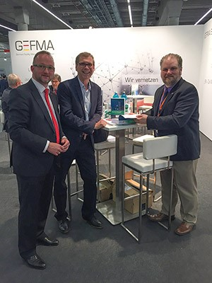 A conference attendee (left) meeting with editors Michael May (center) and Geoff Williams (right) at a book signing event in Frankfurt, Germany